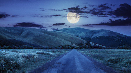 composite landscape with abandoned asphalt road rolls through meadows with flowers going to high  mountains at night in full moon light Foto de archivo