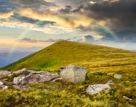composit: composit landscape with white sharp boulders on the hillside near mountain peak in morning light with rainbow