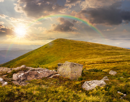 composit: composit landscape with white sharp boulders on the hillside near mountain peak in sunset light with rainbow Stock Photo