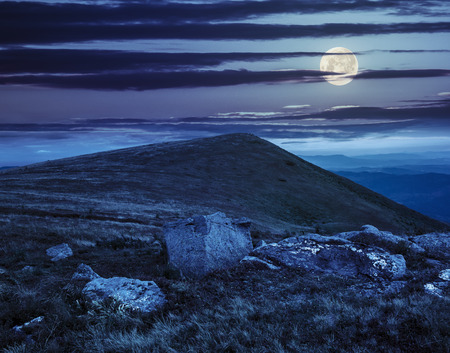 composit: composit landscape with white sharp boulders on the hillside near mountain peak at night in fulll moon light
