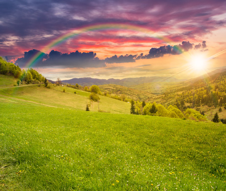 village in mountains behind the agricultural meadow with flowers on  hillside in sunset light with rainbow Stock Photo