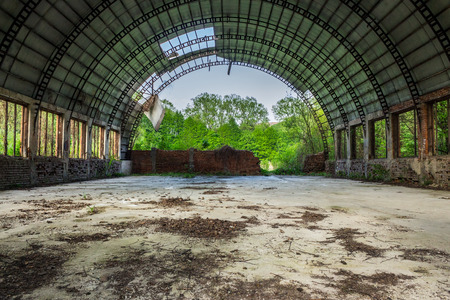 abandoned ruined hangar with broken round roof in the green forest
