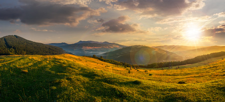 agriculture: agricultural field on hillside in mountains near village in sunset light Stock Photo