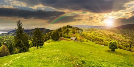 abandoned farm field with ruined barn in mountains near coniferous forest in sunset light with rainbow