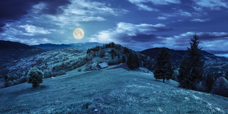 abandoned farm field with ruined barn in mountains near coniferous forest at night in full moon light Stock Photo