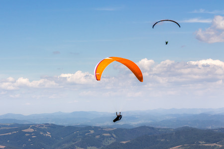 Two persones skydiving  flying over the mountains. parachute extreme sport Stock Photo