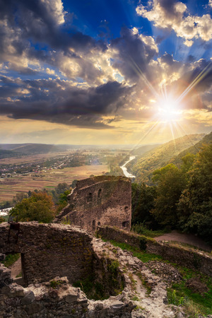 view to village in vally from stone wall of an old ruined castle in the mountains in sunset light Stock Photo