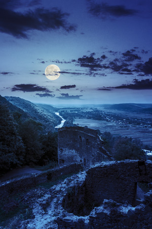 view to village in vally from stone wall of an old ruined castle in the mountains at night in full moon light