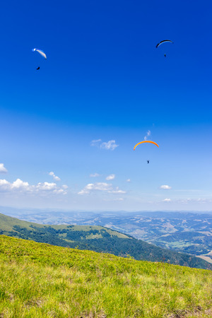 Three persones skydiving  flying over the mountains. parachute extreme sport Stock Photo - 38856943