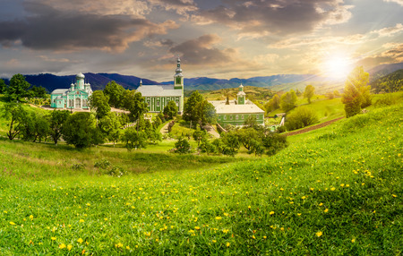 Composite image of green Monastery in mountains on hillside with grass and dandelions in sunset light photo
