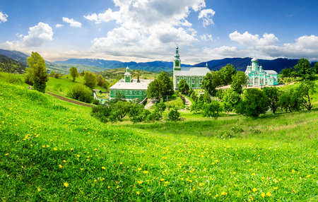 Composite image of green Monastery in mountains on hillside with grass and dandelions in morning light Stock Photo
