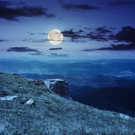 horison: view on high mountains from hillside covered with grass with few stones on the edge at night in full moon light Stock Photo