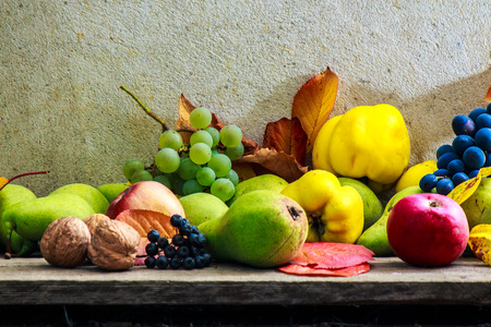 autumnal fruit still life with apples pears quince grapes and leaves on wooden base