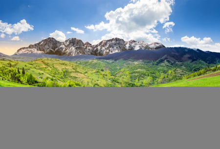 composite summer landscape with 3D mountains. village on agricultural meadow hillside in front of a high rocky mountain range.