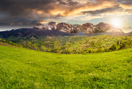 composite summer landscape with 3D mountains. village on agricultural meadow hillside in front of a high rocky mountain range in sunset light Stock Photo