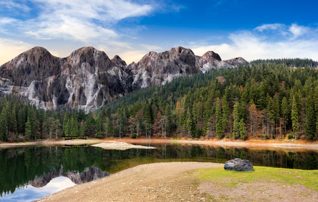 composite landscape with CGI elements. lake with boulder on the shore near the pine forest in mountains with 3D stone peaks Stock Photo