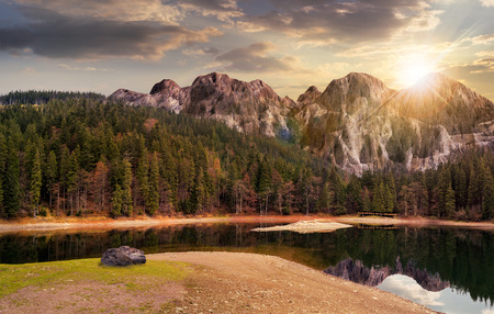 composite landscape with CGI elements. lake with boulder on the shore near the pine forest in mountains with 3D stone peaks in sunset light