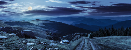 hill range: composite mountain landscape. path through meadow on mountain range with huge boulders near pine forest on hill side at night in full moon light