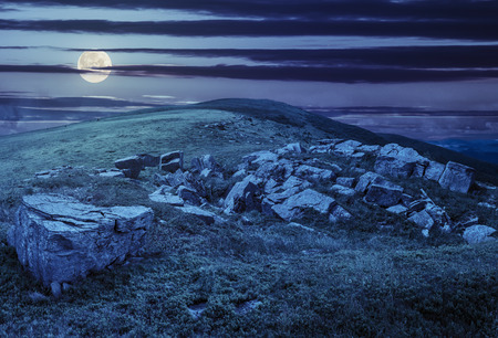 composit: composit landscape with white sharp boulders on the hillside near mountain peak at night in full moon light Stock Photo