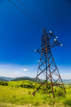 High voltage electric power lines tower over the  mountains Stock Photo