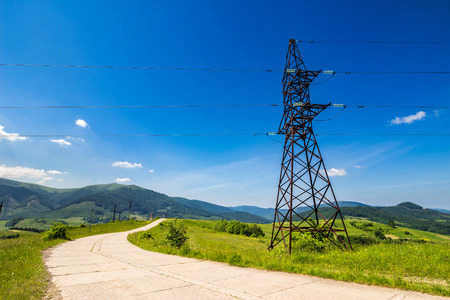 High voltage electric power lines tower near the road in mountains