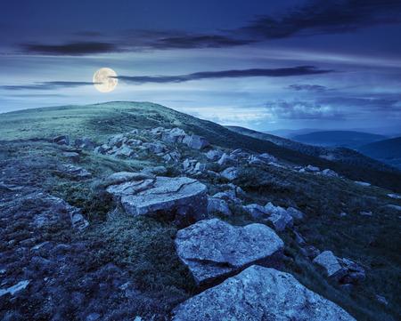 landscape with white sharp boulders on the hillside near mountain peak at night in full moon light
