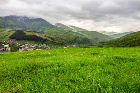 village near meadow with dandelions at the foot of a mountain range with fog and clouds on the top in spring time Stock Photo