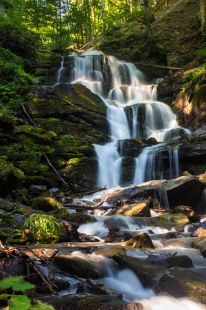 big waterfall with huge boulders in green forest on summer morning Stock Photo
