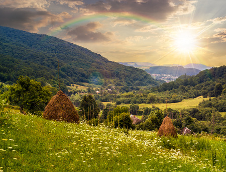 haystack  on a green agricultural meadow in the mountains with rainbow  in evening light Stock Photo