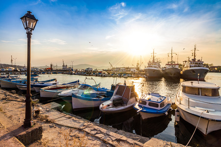 small fishing boats and few big one docked near embankment in port of Bulgarian town Sozopol in evening light