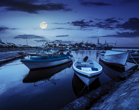 small fishing boats and few big one docked near embankment in port of Bulgarian town Sozopol at night in full moon light Stock Photo - 44248320