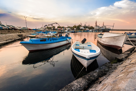 small fishing boats and few big one docked near embankment in port of Bulgarian town Sozopol in morning light
