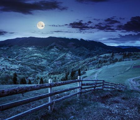 presto paesaggio autunnale. recinzione sul prato agricolo nei pressi sentiero sul fianco della collina. foresta nella nebbia sulla montagna di notte alla luce della luna piena