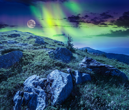 full: white sharp boulders on the grassy hillside on the peak on high mountain range at night in full moon and Northern Lights. composite landscape