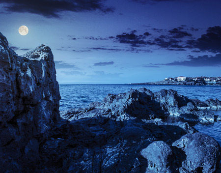 sea coast  with giant boulders opposite to the old city on the other side of the bay at night in full moon light