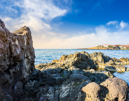 sea coast  with giant boulders opposite to the old city on the other side of the bay at sunrise Stock Photo