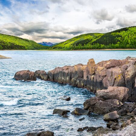 composite image of summer landscape  on lake with rocky shore and some boulders near forest in mountain  with high peak far away in morning light