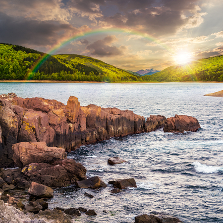 composite image of summer landscape  on lake with rocky shore and some boulders near forest under the rainbow  in mountain  with high peak far away in evening light