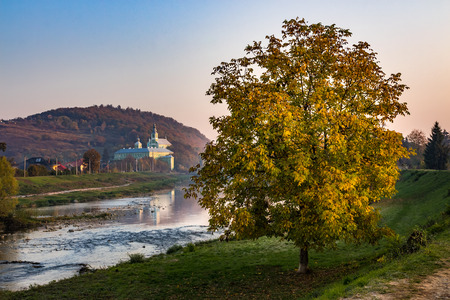 Monastery on a hill near river at the foot of the mountain. tree with yellow foliage on near river in warm light of hazy autumn sunrise