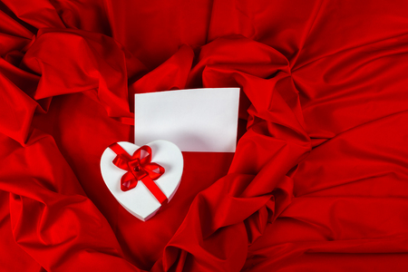 love card. white greeting card and  heart with a red ribbon on a red fabric