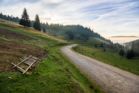 broken fence near place where sheeps are shaved  on meadow by the road in mountains with conifer forest in fog at sunrise Stock Photo