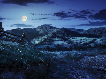 wooden fence in the grass on the hillside near the village at night in full moon light Stock Photo