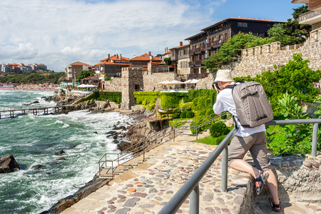 young photographer with backpack  making shots of ancient european town Sozopol on a rocky shore near sea in summer Stock Photo