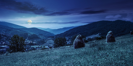 row of haystacks on the hillside meadow near the village in mountains at night in full moon light Stock Photo