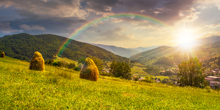 row of haystacks on the hillside meadow under the rainbow near the village in mountains at sunset Stock Photo