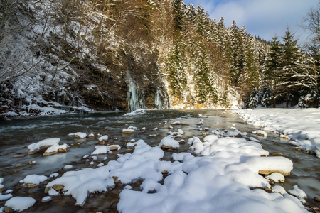 frozen waterfall on the  river among forest with conifer trees and snow on the ground