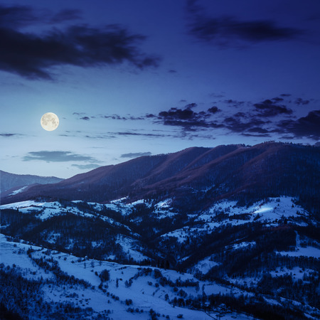 village in mountains covered with snow at night under full moon light