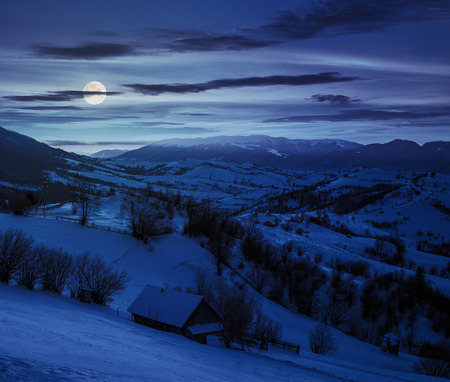 few houses of village on hillside in mountain area at night in full moon light