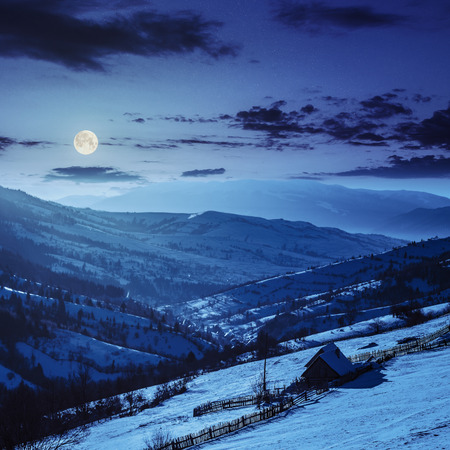 woodshed behind the fence on the hillside cowered with snow nearconifer forest in winter mountains at night in full moon light