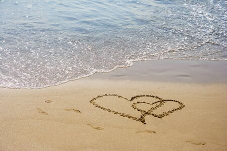 hearts couple drawn on the sand of a sea beach with few human steps oround them